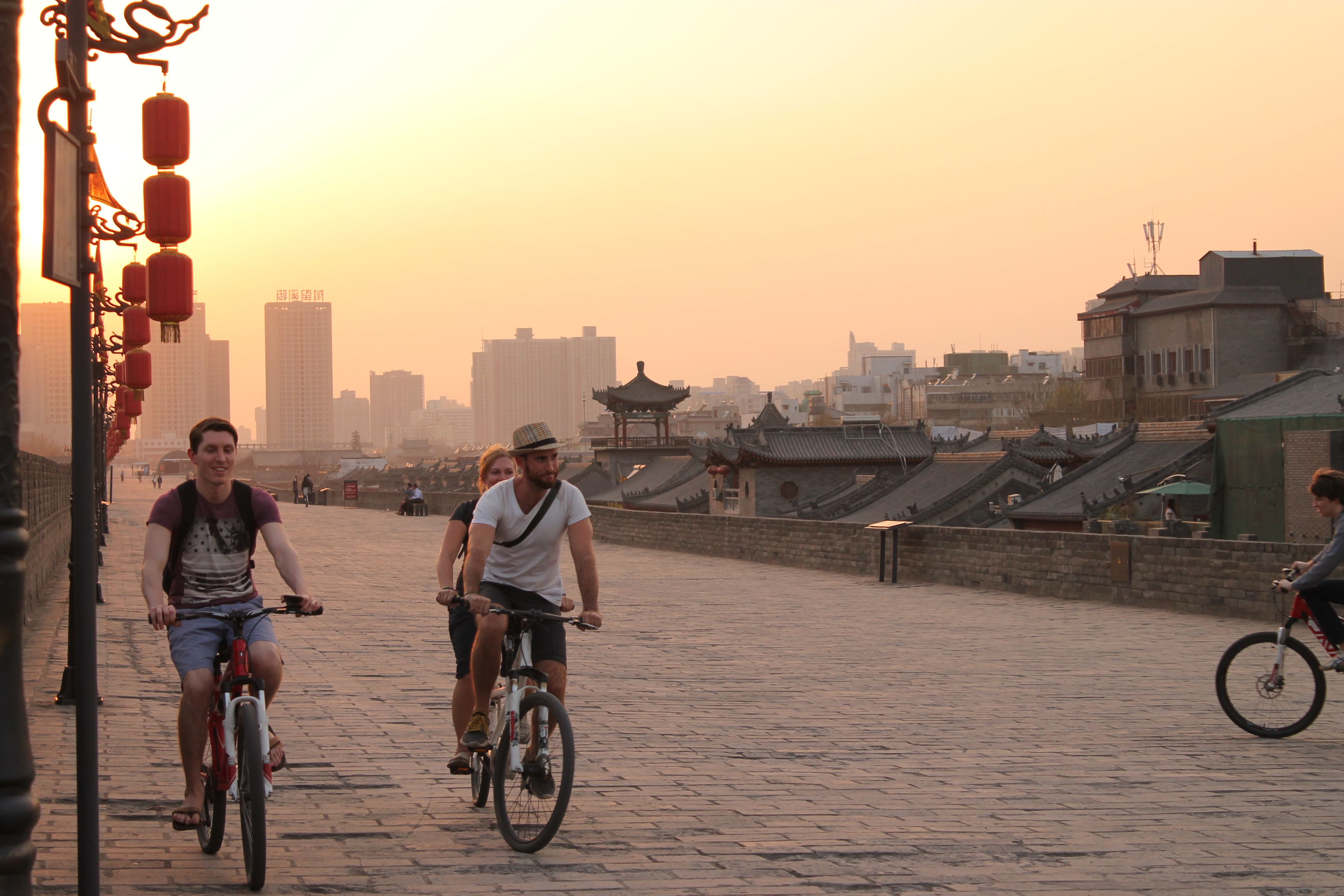 interns riding bikes on the ancient wall of Xi'an